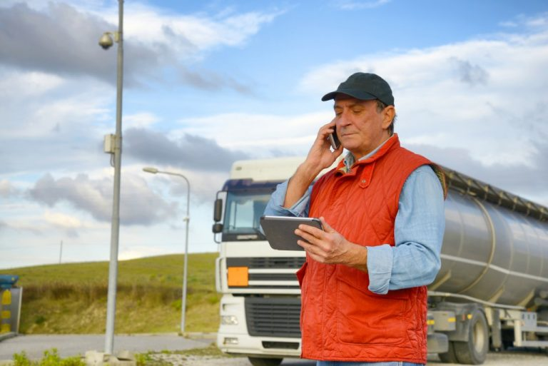 Truck driver using his cellphone and ipad
