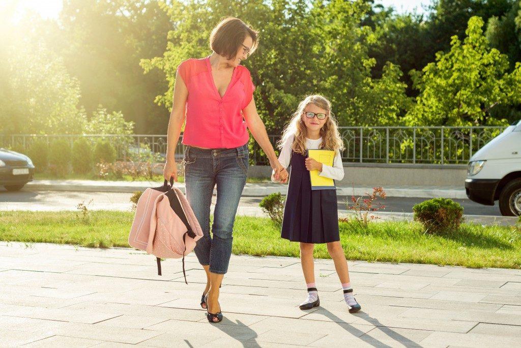 Mother walking her daughter to her new school
