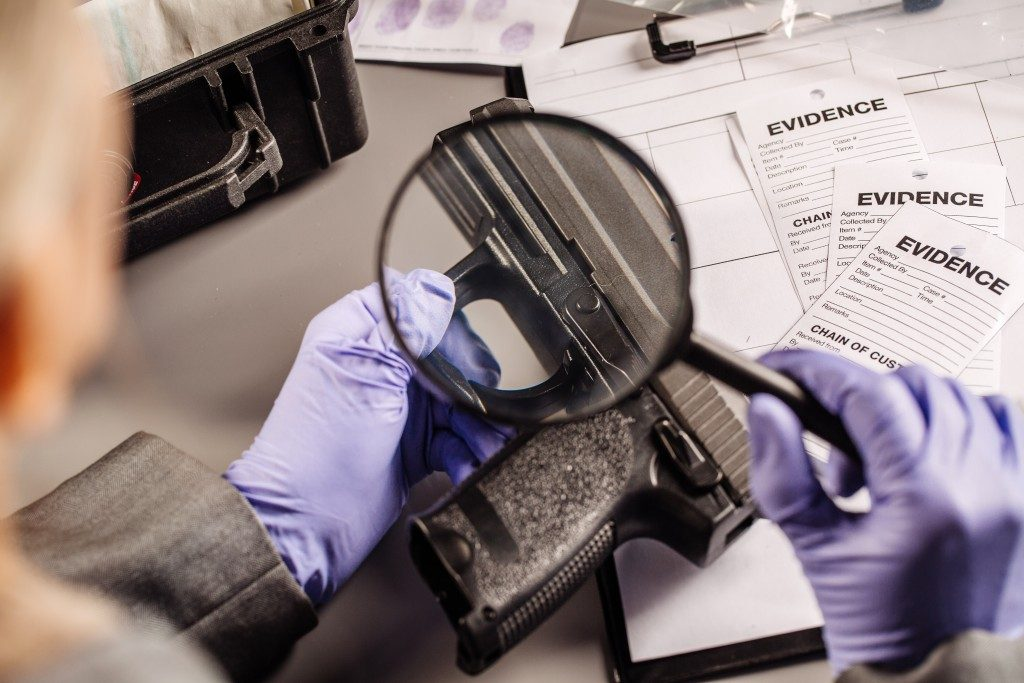 investigator checking finger print on the weapon