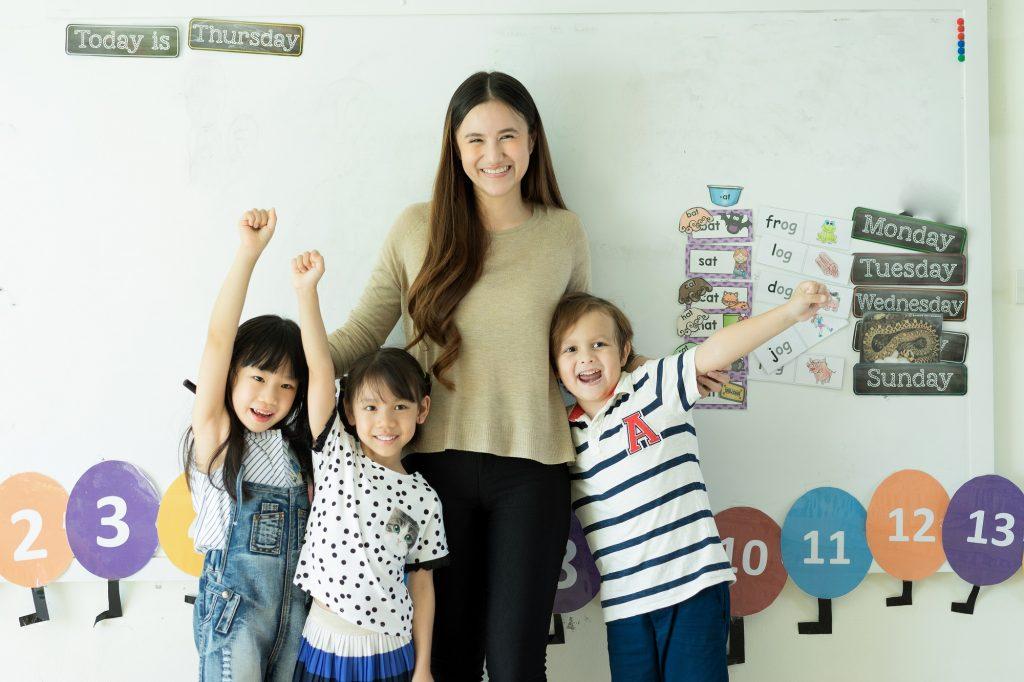 happy teacher with little kids in school